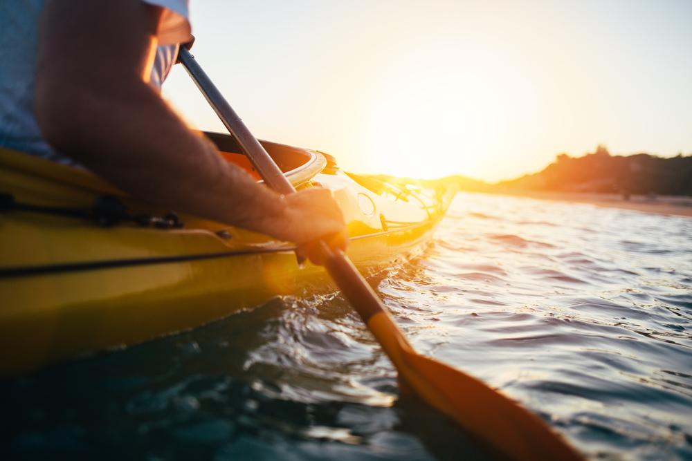 kayaker balancing in kayak